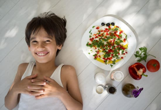 Boy Smiling With Mediterranean Meal