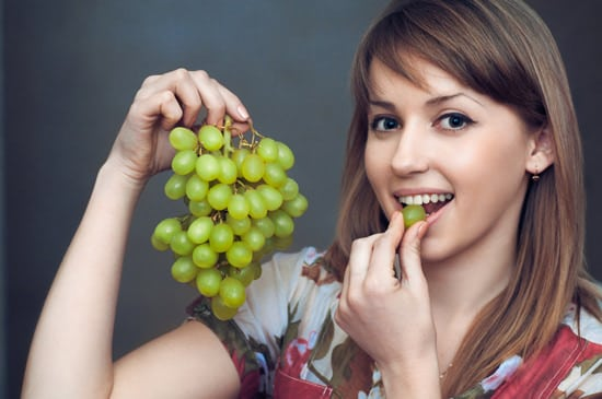 Young Woman Eating Green Grapes